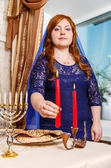 Eine jüdische frau, deren kopf mit einem blauen umhang bedeckt ist, zündet kerzen an einem passahabend-tisch an