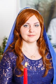 Eine jüdische frau mit einem blauen umhang steht neben einer brennenden kerze