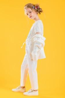 Eine jugendliche in der weißen kleidung, die auf gelb aufwirft