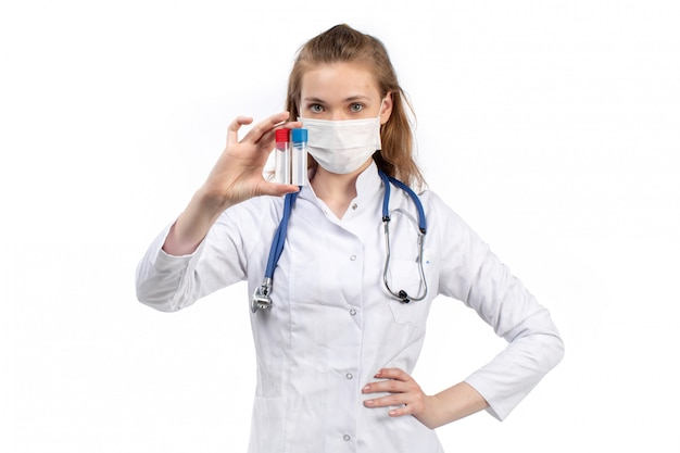 Eine junge ärztin der vorderansicht im weißen medizinischen anzug mit stethoskop, das weiße schutzmaske trägt, die halteflaschen auf dem weiß aufwirft