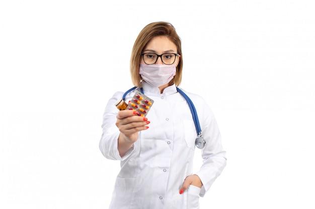 Eine junge ärztin der vorderansicht im weißen medizinischen anzug mit stethoskop, das weiße schutzmaske trägt, die pillen auf dem weiß hält