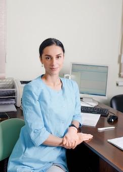 Eine junge ärztin sitzt in ihrem büro und wartet auf einen patienten und lächelt