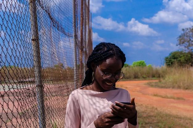 Eine junge afrikanische dame, die ihr handy bedient