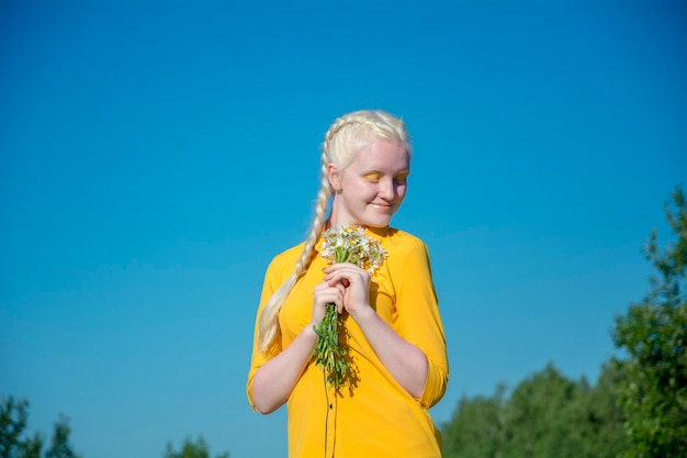 Eine junge albino-frau in einer gelben bluse gegen einen blauen himmel. hält einen strauß gänseblümchen in sich