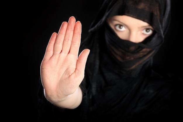 Eine junge arabische frau, die zum stopp bei schwarz zeigt