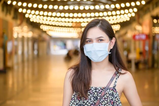 Eine junge asiatische frau trägt schutzmaske beim einkaufen im einkaufszentrum, coronavirus-schutz, neues normales lebensstilkonzept