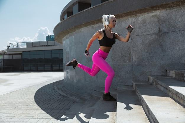 Eine junge athletische frau im hemd und in den weißen kopfhörern, die trainieren, die musik auf der straße draußen zu hören. treppen hoch rennen. konzept des gesunden lebensstils, des sports, der aktivität, des gewichtsverlusts.