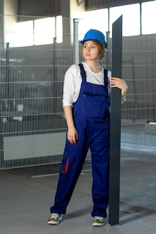 Eine junge attraktive dame der vorderansicht im blauen bauanzug und im helm arbeiten, die schweres metallisches detail während des tages halten, das in die fernbau-architekturkonstruktion schaut