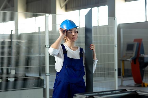 Eine junge attraktive dame der vorderansicht im blauen bauanzug und im helm, die das schwere metallische detail während des architekturbaus der tagesgebäude halten