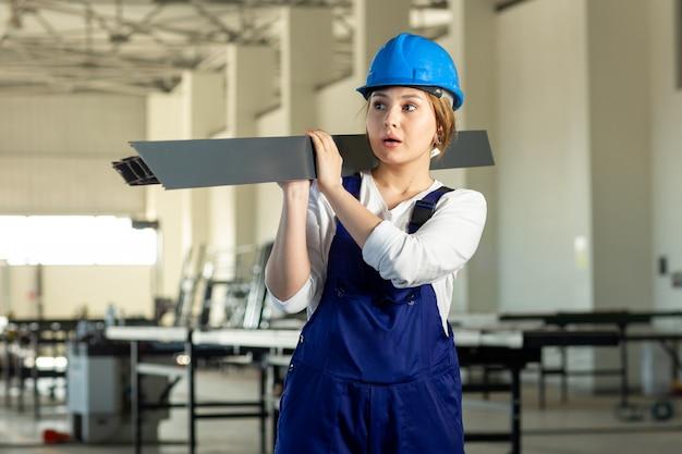 Eine junge attraktive dame der vorderansicht im blauen bauanzug und im helm, die schweres metallisches detail während der tagsüber überraschten gebäudearchitekturkonstruktion halten