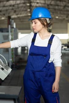 Eine junge attraktive dame der vorderansicht im blauen bauanzug und in den helm, die maschinen im hangar steuern, der im bereich gebäudearchitekturbau arbeitet