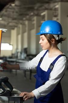 Eine junge attraktive dame der vorderansicht im blauen bauanzug und in den helm, die maschinen im hangar während des architekturbaus der tagesgebäude steuern