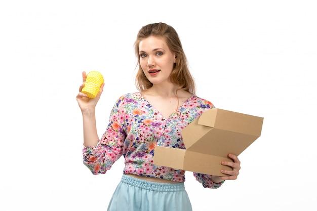 Eine junge attraktive dame der vorderansicht im bunten blumendesignhemd und im blauen rock, die gelbes geschenk vom kleinen paket auf dem weiß erhalten