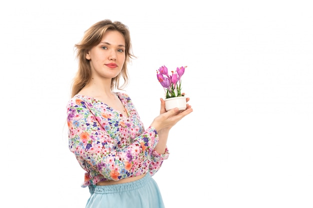 Eine junge attraktive dame der vorderansicht im bunten blumendesignhemd und im blauen rock, die lila blumenpflanze auf dem weiß halten
