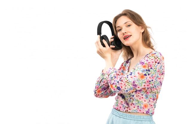 Eine junge attraktive dame der vorderansicht im bunten blumendesignhemd und im blauen rock, die schwarze kopfhörer auf dem weiß halten