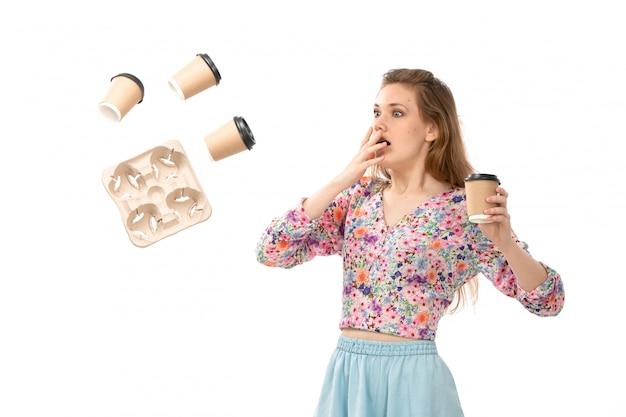 Eine junge attraktive dame der vorderansicht im bunten blumendesignhemd und im blauen rock mit geworfenen kaffeetassen überrascht auf dem weiß