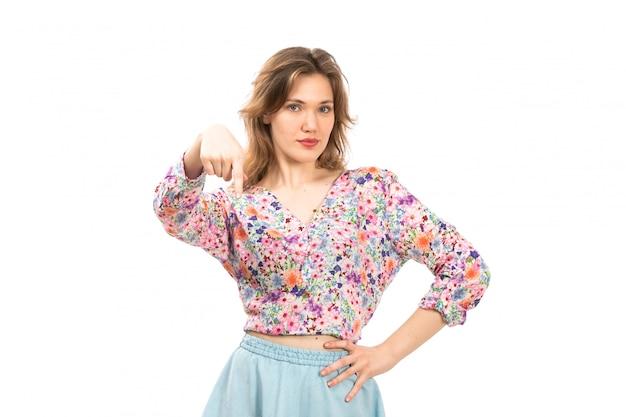 Eine junge attraktive dame der vorderansicht im bunten blumendesignhemd und im blauen rockhandausdruck auf dem weiß