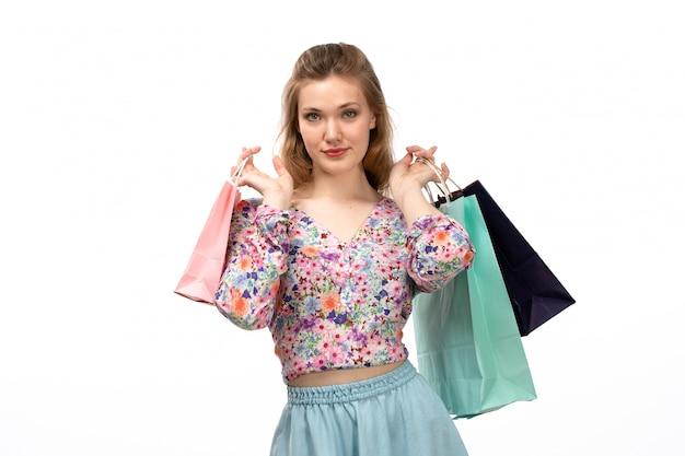Eine junge attraktive dame der vorderansicht im bunten blumenentwurfshemd und im blauen rock, die einkaufspakete auf dem weiß halten