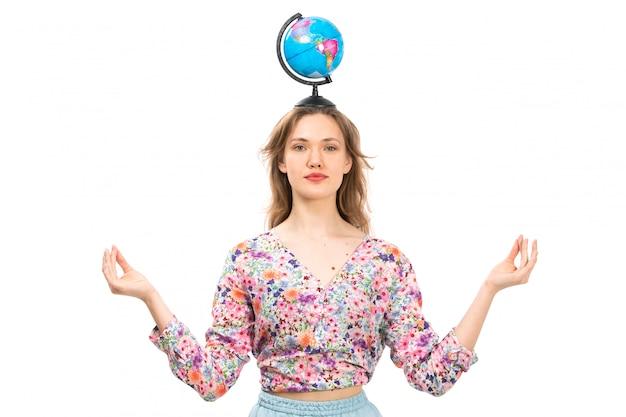 Eine junge attraktive dame der vorderansicht im bunten blumenentwurfshemd und im blauen rock, die kleinen globus auf ihrem kopf halten, der über das weiß meditiert