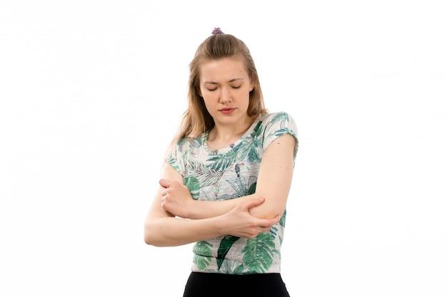 Eine junge attraktive dame der vorderansicht im entworfenen hemd und im schwarzen rock, die unter schmerzen in ihren armen auf dem weiß leiden