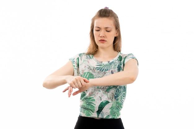 Eine junge attraktive dame der vorderansicht im entworfenen hemd und in der schwarzen hose, die unter handgelenksschmerzen auf dem weiß leiden