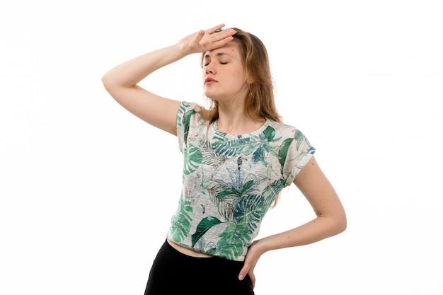 Eine junge attraktive dame der vorderansicht im entworfenen hemd und in der schwarzen hose, die unter kopfschmerzen und temperatur auf dem weiß leiden