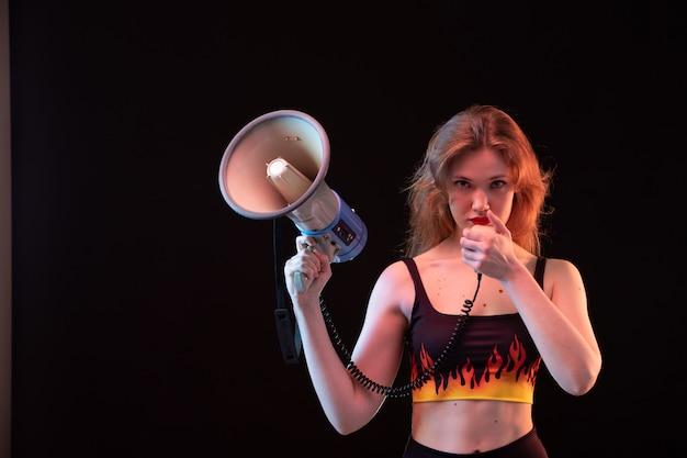 Eine junge attraktive dame der vorderansicht im feuerhemd und in der schwarzen hose, die megaphon auf dem schwarzen hintergrundlautstärke laut verwendet