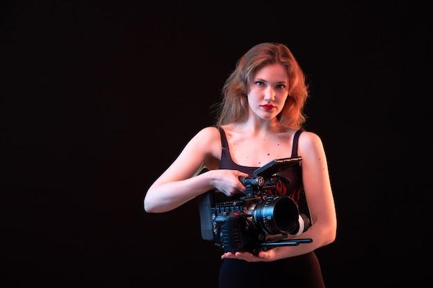 Eine junge attraktive dame der vorderansicht im feuerhemd und in der schwarzen hose, die schwarze videokamera auf der aufnahme des schwarzen hintergrunds halten