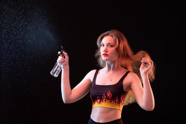 Eine junge attraktive dame der vorderansicht im feuerhemd und in der schwarzen hose unter verwendung des reinigungssprays auf der schwarzen hintergrundsprayreinigung