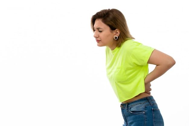 Eine junge attraktive dame der vorderansicht im grünen hemd und in den blauen jeans, die unter den rückenschmerzen auf dem weiß leiden