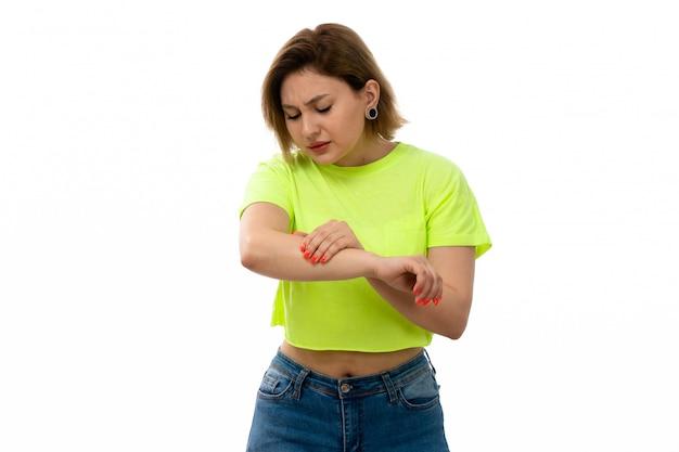 Eine junge attraktive dame der vorderansicht im grünen hemd und in den blauen jeans, die unter handschmerz auf dem weiß leiden