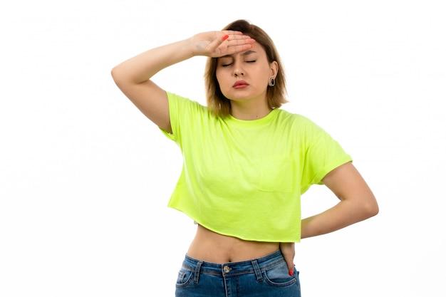 Eine junge attraktive dame der vorderansicht im grünen hemd und in den blauen jeans, die unter hoher temperatur auf dem weiß leiden
