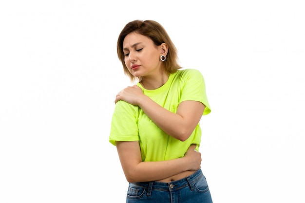 Eine junge attraktive dame der vorderansicht im grünen hemd und in den blauen jeans, die unter schulterschmerzen auf dem weiß leiden