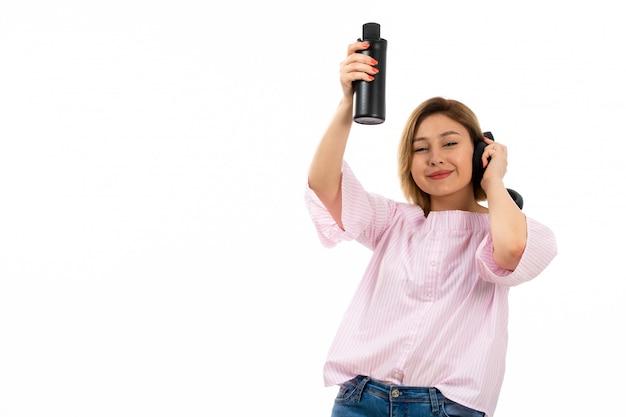 Eine junge attraktive dame der vorderansicht im rosa hemd und in den blauen jeans mit den schwarzen kopfhörern, die schwarze thermoskopf-schwarze ohrhörer trinken, die auf dem weiß lächeln