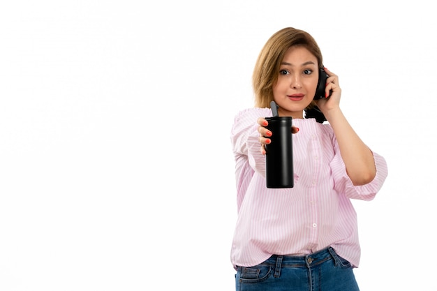 Eine junge attraktive dame der vorderansicht im rosa hemd und in den blauen jeans mit den schwarzen kopfhörern, die schwarze thermosschwarzkopfhörermusik auf dem weiß halten