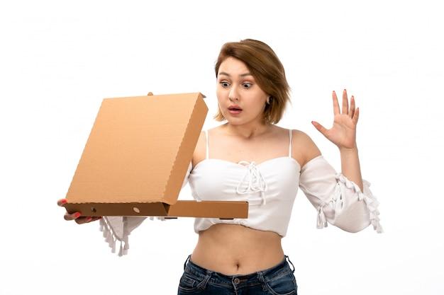 Eine junge attraktive dame der vorderansicht im weißen hemd und in den blauen jeans, die braunes paket halten, das es auf dem weiß schlecht überrascht öffnet