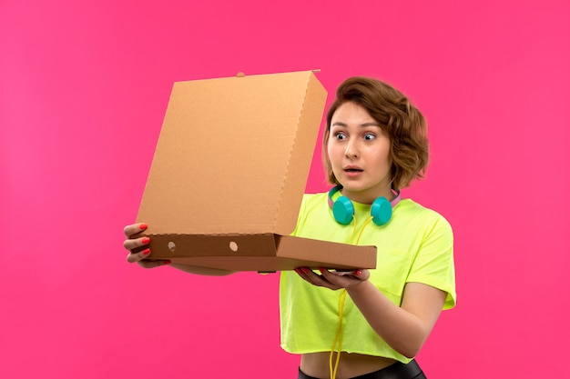 Eine junge attraktive frau der vorderansicht in den blauen kopfhörern der schwarzen hose des säurefarbenen hemdes, die braune box auf der jungen weiblichen musik des rosa hintergrunds öffnen