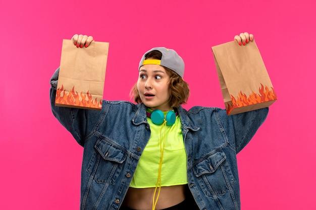 Eine junge attraktive frau der vorderansicht in der säureharbenen schwarzen hosenjeans der hemdhülle, die die bunte tasche der braunen box auf der jungen weiblichen mode des rosa hintergrunds hält