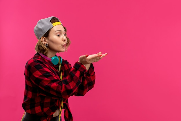 Eine junge attraktive frau der vorderansicht in der schwarzen hose des karierten rot-schwarzen hemdes mit blauen kopfhörern, die das senden von luftküssen auf der jungen weiblichen mode des rosa hintergrunds aufwirft