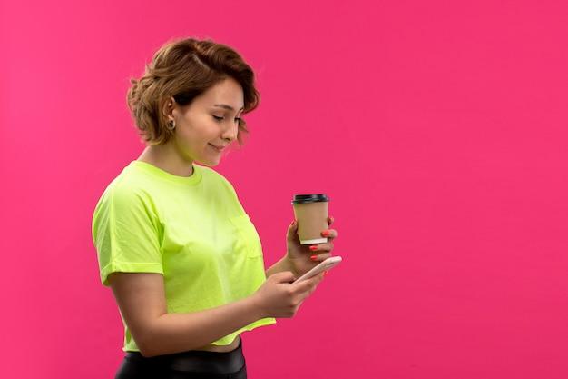 Eine junge attraktive frau der vorderansicht in der schwarzen hose des säurefarbenen hemdes unter verwendung des telefonhaltens kaffeetasse auf den jungen weiblichen technologien des rosa hintergrunds