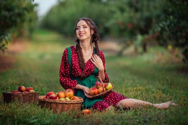 Eine junge attraktive frau in einem grünen kleid mit roter schürze pflückt reife äpfel in weidenkörben im apfelgarten.