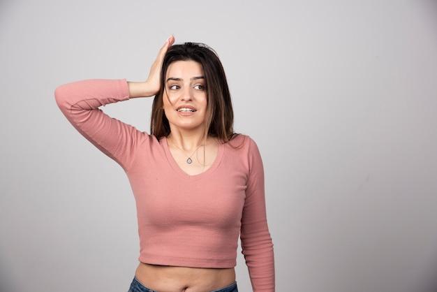 Eine junge attraktive frau in freizeitkleidung mit erhobener handfläche auf dem kopf.