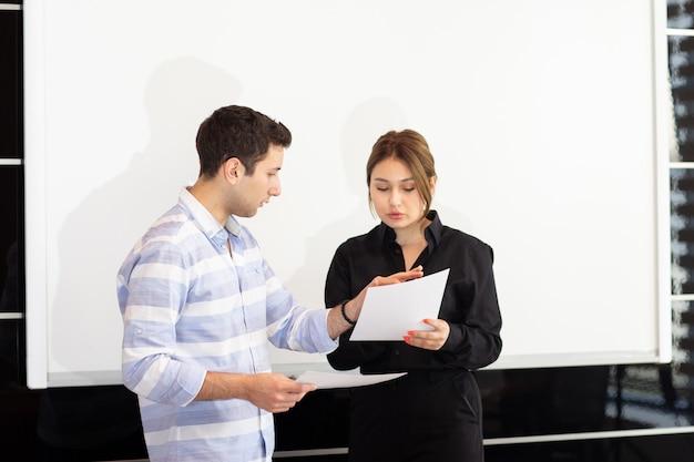 Eine junge attraktive geschäftsfrau der vorderansicht im schwarzen hemd zusammen mit dem jungen mann, der grafiken auf dem schreibtisch bespricht, während junge dame ihre arbeit darstellt, die dokumentjobaufbaupräsentation liest