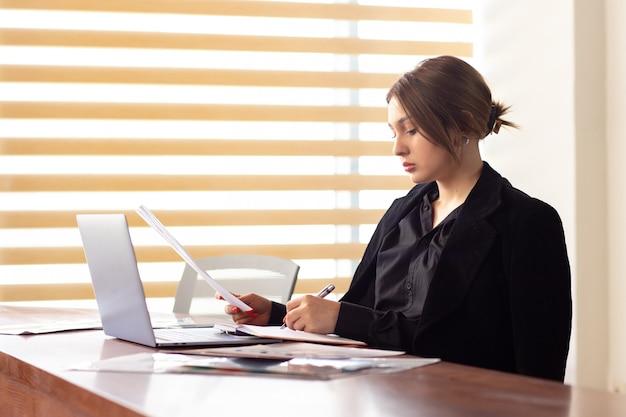 Eine junge attraktive geschäftsfrau der vorderansicht in der schwarzen jacke des schwarzen hemdes unter verwendung ihrer silbernen laptop-schreiblesung, die in ihrem büroarbeitsjobgebäude arbeitet