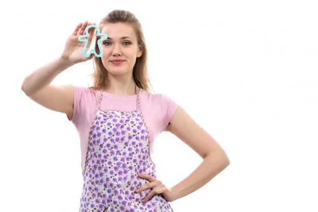 Eine junge attraktive hausfrau der vorderansicht des bunten umhangs des rosa hemdes, der lächelnd das kleine blaue menschlich geformte spielzeug auf dem weißen hintergrundküchenküchen weiblich hält