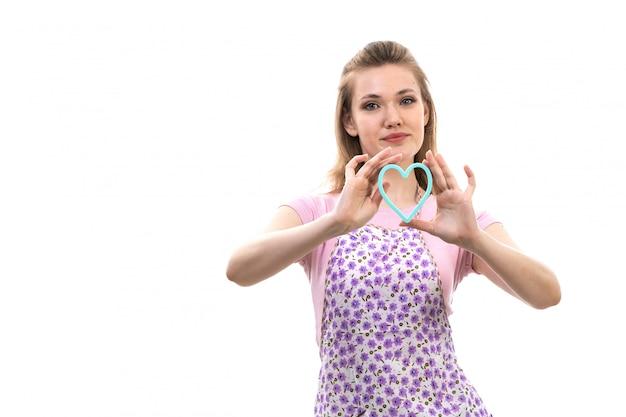 Eine junge attraktive hausfrau der vorderansicht des bunten umhangs des rosa hemdes, der lächelnd die kleine blaue herzform auf der weißen hintergrundküchenküche weiblich hält