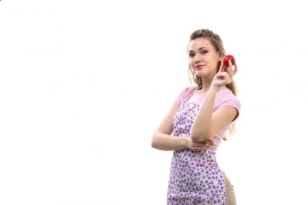 Eine junge attraktive hausfrau der vorderansicht des bunten umhangs des rosa hemdes, der rote tomate hält, die auf der weißen hintergrundküchenküchenfrau posiert