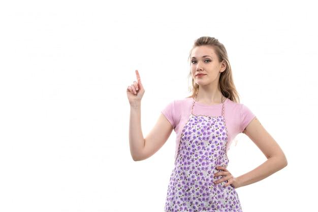 Eine junge attraktive hausfrau der vorderansicht im bunten umhang des rosa hemdes, das auf der weißen hintergrundküchenküchenfrau aufwirft