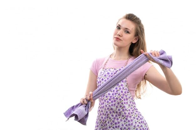 Eine junge attraktive hausfrau der vorderansicht im bunten umhang des rosa hemdes, das lächelndes lila handtuch auf der weißen hintergrundküchenküche weiblich hält
