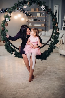 Eine junge attraktive mutter mit langen dunklen haaren im schwarzen kleid hält ihre kleine kaukasische tochter in den armen und sitzt in einer großen runden weihnachtsdekoration aus fichtenzweigen und lächelt
